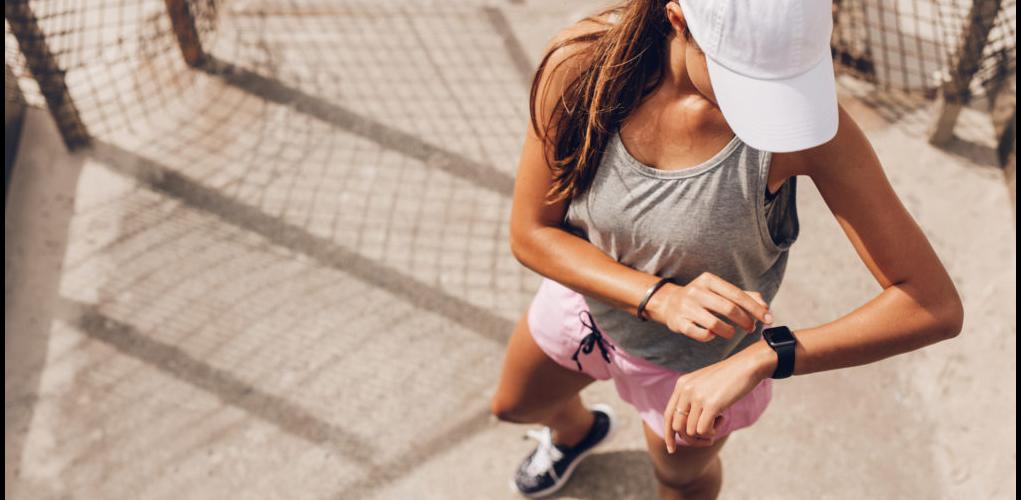 sporthorloge dame kijkt op horloge tijdens hardlopen